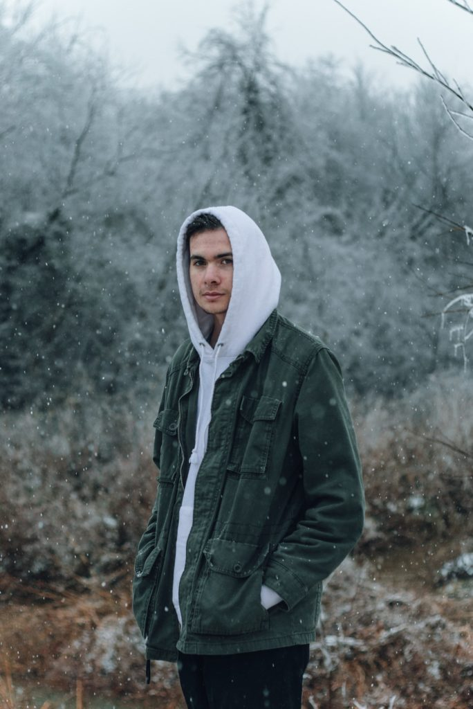 Man standing in the snow looking sad, feeling the effects of seasonal depression.