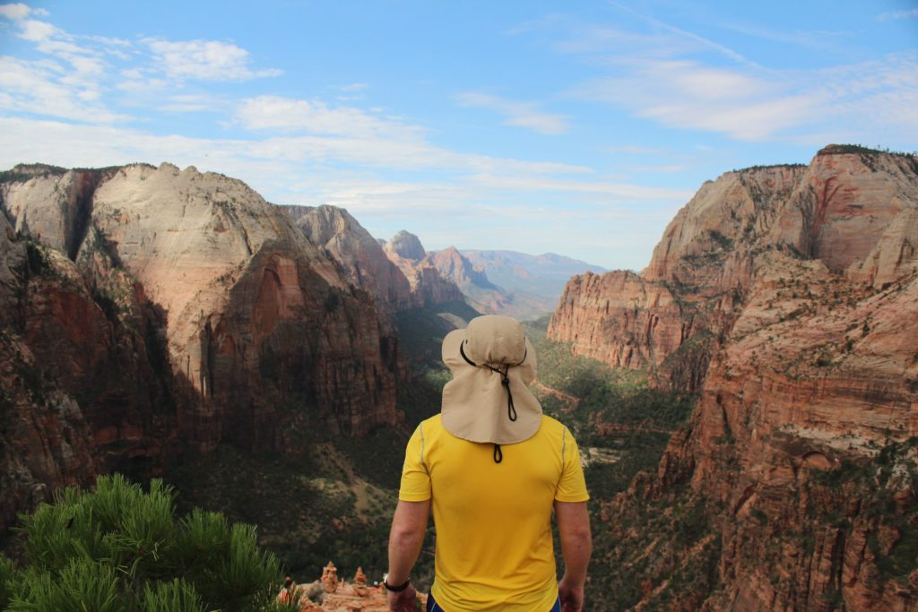 Man exercising wearing bright yellow shirt and tan hat looking out over a canyon.