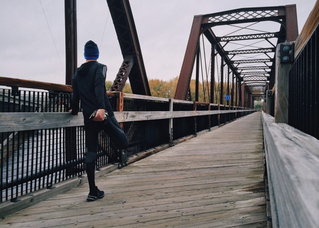 Man stretching on a bridge, about to exercise to help with his anxiety.