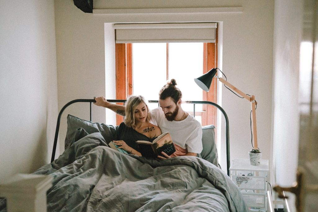 Man and woman laying in bed together talking about anxiety and reading a book.